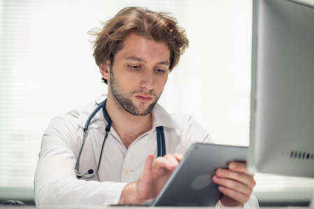 A young male doctor sitting at his desk in the office, checking the schedule on his tab.