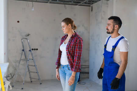 The builder shows the female customer the renovation of the apartment. She is unhappy 版權商用圖片