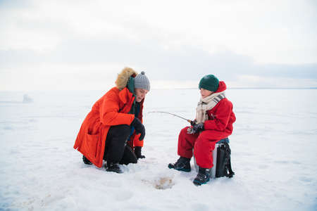 Father and son in red winter clothes came to fish on the river bank in winter. Banque d'images