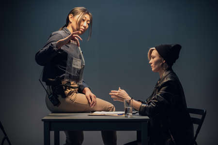 An experienced investigator during an interrogation at a police station shows the criminal girl the found crime weapon.