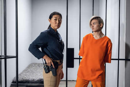 Asian warden and a female prisoner in a high-security prison stand in front of an open cell