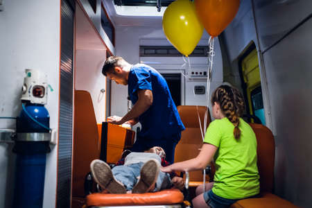 EMT in a blue uniform searching for some supplies in a medical kit, a young woman lyng on a stretcher with an oxygen mask, a small girl sitting beside her. 版權商用圖片