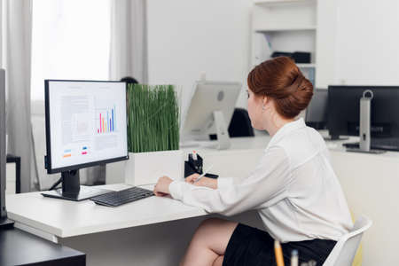 Girl Manager in a white blouse at the computer calculates the profit and loss of the company, builds charts