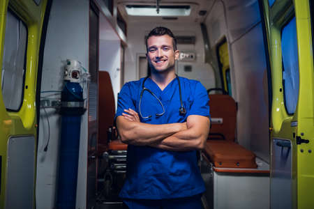 Doctor in a medical uniform standing and looking at the camera with a toothy smile.