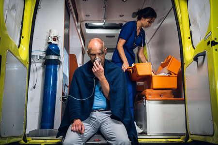 Injured man sitting with an oxygen mask on in an ambulance car, a nurse checking her medical kit in the background.