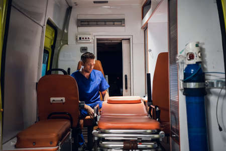 Young doctor in a uniform sitting in the ambulance car.