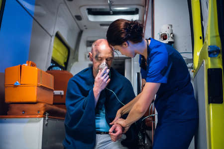 A female paramedic providing first aid to an injured man resqued from the fire, checking his pulse.
