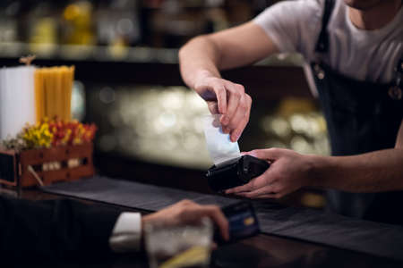 the bartender accepts payment by credit card at the bar.
