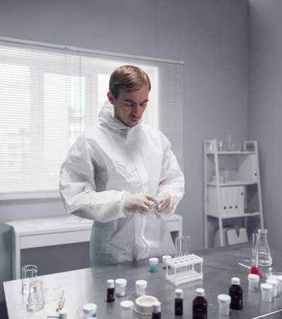 A researcher doing a chemical test in the laboratory, mixing some substances.
