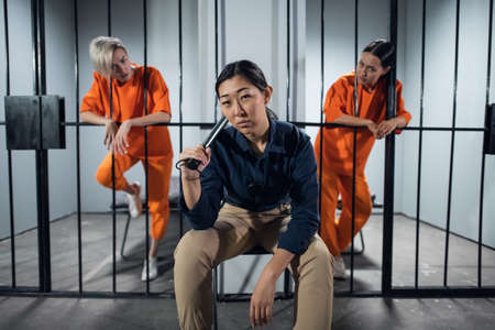 Asian womens prison. In the cell there are two young girls convicted of a criminal offense and a female warden in a guards uniform.