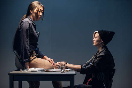 A female investigator sits on a table and interrogates a young criminal in an interrogation room. Reklamní fotografie