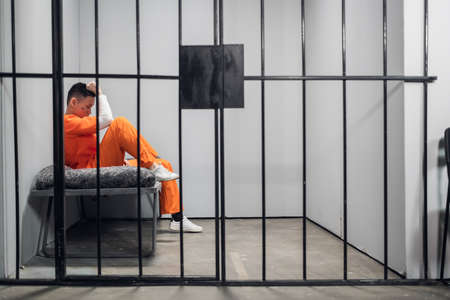 Solitary cell with a criminal in an orange robe in an asian prison. Copy space. Sad emotions of a young guy
