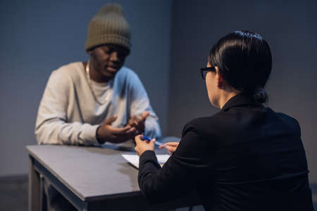A lawyer girl with glasses and a young black guy communicate in the interrogation room about the grounds for his detention.