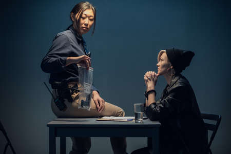 A young asian female investigator sits on a table and shows a package of weapons to a blonde suspect.