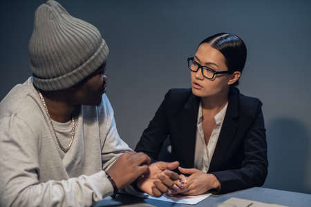 In the interrogation room, a suspect in a drug distribution and possession case consults with a public defender.