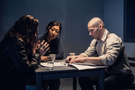 A police detective at the station and his partner, an asian woman, present evidence to a male suspect in an interview room
