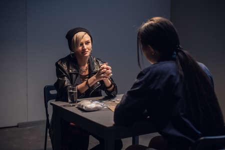 An investigator interrogates a suspected drug dealer in an interrogation room.