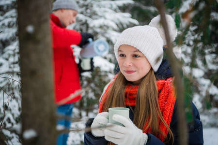 A young long-haired blonde girl drinks tea from a mug in the winter forest. Portrait with depth of field against the background of fir trees and snowdrifts