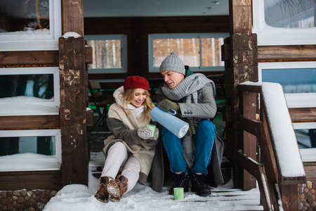 After a walk through the winter forest, the young couple sat on the porch of the house, to drink tea from a thermos and warm up.