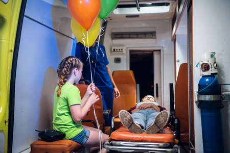 Ambulance car, a paramedic stands beside an unconscious woman lying on stretcher, her little daughter sits nearby. Standard-Bild