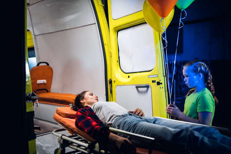 Little girl standing beside her mother, who is lying on a stretcher next to an ambulance, the woman is trying to calm down her daughter.