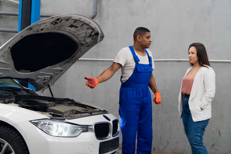 Mechanic and client inspect engine of car. Car hood open