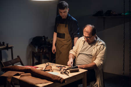 father-shoemaker prepares a successor in the family business of manual production of shoes in the workshop in his house