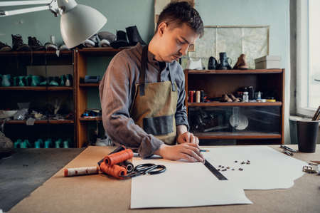 A young shoemaker makes a drawing for a pattern for leather shoes on a table in his workshop. Stock fotó