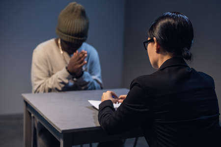 At the police station, a girl investigator interrogates a black guy who is sitting in front of her in handcuffs.