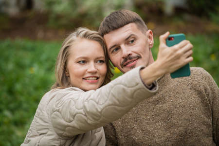 Close-up portrait of a young couple taking a selfie on the front camera of a smartphone in nature outdoors. Funny and cute emotions