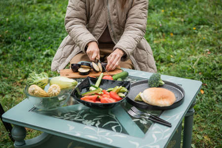 An unrecognizable woman cuts vegetables at a table in the backyard of her dacha, preparing for a picnic with her family on a weekend in early autumn. Stok Fotoğraf
