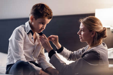 A Mother helping her son to get ready for school, fixing his collar.