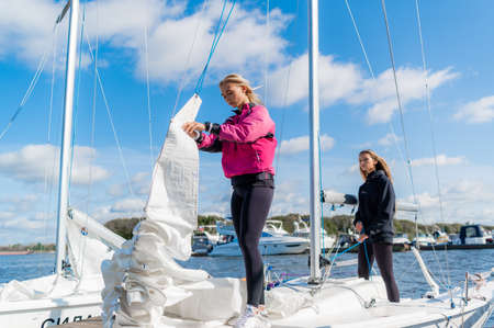 Two young female athletes prepare a sailing boat for the regatta on the river pier. Banque d'images