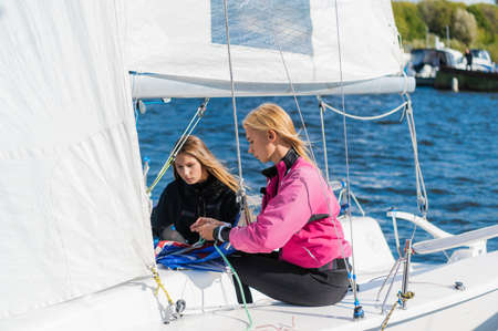 Before the competition on sailing boats two cute girls athletes equip their sailing yacht.