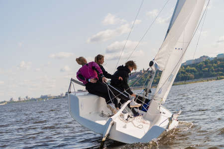 A mixed crew of a sports yacht participates in sailing competitions on the river. One man and two girls Banque d'images