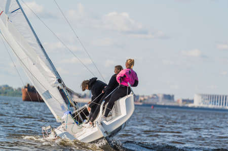 A beautiful picture with a sports yacht on the background of an urban landscape floating under full sails on a wide river