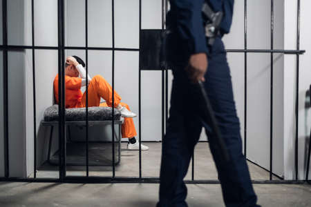 A prison guard makes a tour of the cells in a high-security prison. The cells are occupied by criminals in red robes
