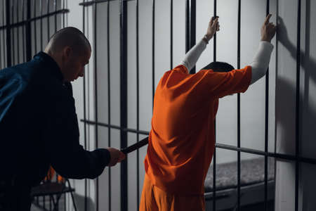 An armed guard searches a newly arrived criminal in a prison corridor against a backdrop of bars