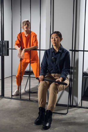 A normal day in a womens prison, a female warden is on guard for a female criminal. Banque d'images
