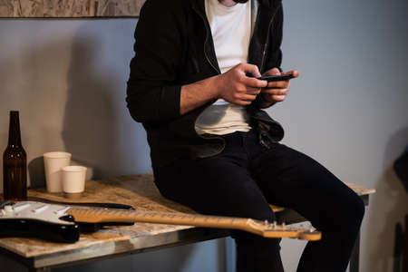 in a music Studio a guy sits on a table and plays a video game on his phone after a rehearsal
