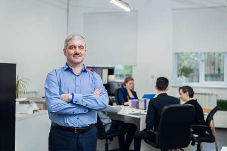 A portrait of a successful smiling senior businessman with his hands folded, his young team is on the background having a meeting in their office.