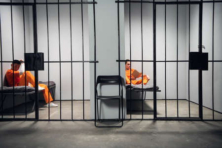 Prisoners in their cells are bored before lights out in prison. Read books. Symmetrical composition. Copy space.