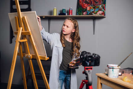 a young blogger girl at home leads a remote masterclass on drawing pictures during quarantine