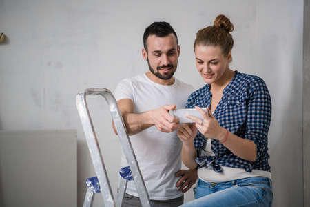 Woman and man sitting on a stepladder and looking at photos on the phone