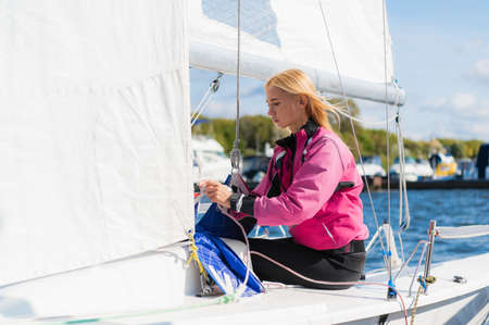 Young athletic girl in sports clothes on a yacht in the dock is ready for a sailing regatta