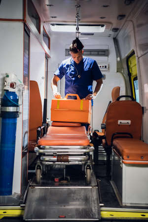 A young doctor in a medical uniform packs his medical bag in the ambulance car.