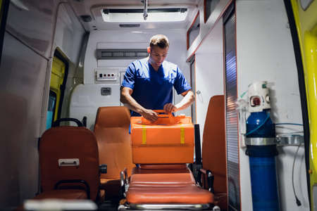 Young doctor preparing his medical kit in the ambulance car.