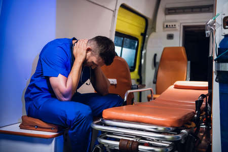 Exhausted paramedic having a little break, sitting in an ambulance car.