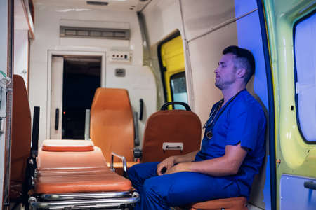 Tired paramedic on duty, sitting in an ambulance car, waiting for the next call.
