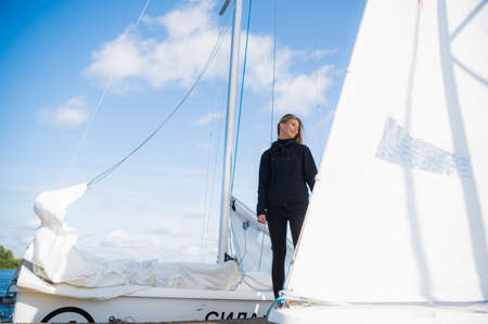 Cute girl in black sportswear stands on a yacht against the blue sky in windy weather.